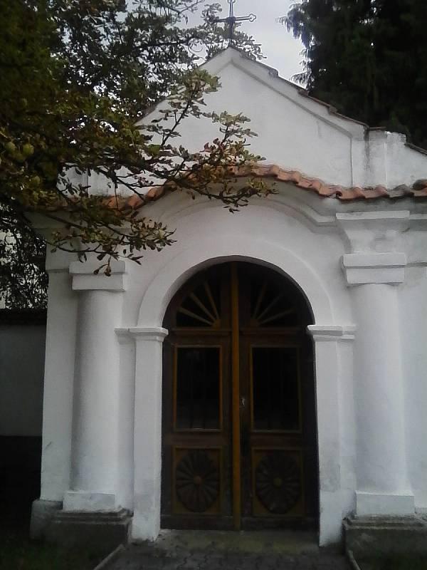 Výklenková kaple ve zdi u kostela.