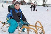 Nedělní dopoledne na svahu v Brodské ulici trávil na sáňkách také Dominik.
