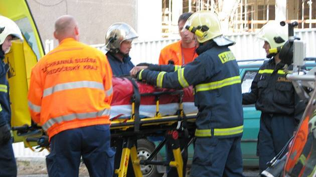 Hasiči s pomocí vysokozdvižné plošiny pomáhali záchranářům přepravit zraněného dělníka ze staveniště v příbramské nemocnici k sanitce.