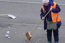 Zaměstnankyně technických služeb uklízí nepořádek v JIrsákových sadech po řidičích, kteří jednoduše vysypou obsah popelníků na zem.