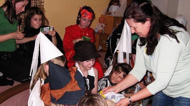 Zaměstnankyně knihovny Jana Adamcová vyzvala děti v maskách – čerty, bílé paní, loupežníky, černokněžníky..., aby si sáhly pro odměnu do kouzelné torničky.