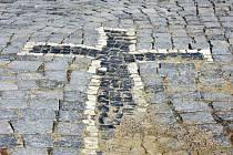 Kříž na náměstí v Novém Kníně vyskládaný z barevných dlaždic.