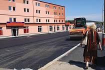 Dělníci pokládají nový asfaltový koberec před bytovým domem v Příbrami