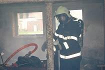 Hasiči vyhazují ze stodoly ještě doutnající kusy dřeva a kontrolují, zda mají oheň úplně pod kontrolou. Díky včasnému zásahu se oheň nerozšířil