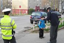 Policie učí školáky přecházet ulici.