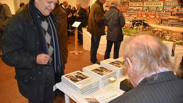 Josef Velfl podepisuje knihu.