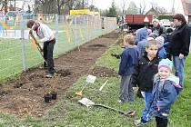 V DOBĚ, kdy jabloně byly ještě na cestě, sledovaly děti se zájmem výsadbu keřů u plotu nového hřiště.
