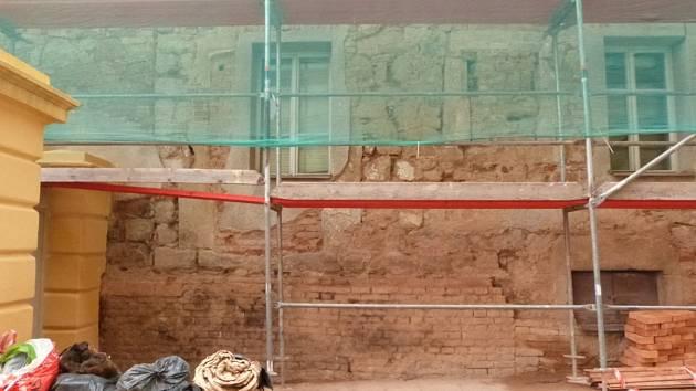 Část dvorní fasády s torzem vchodového kamenného portálu vlevo a kompletním okénkem vpravo s rovným nadpražím, Omáčkovna v Rakovníku.