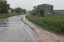 Voda splavená na silnici od Vlkova před Hořesedlemi v sobotu odpoledne