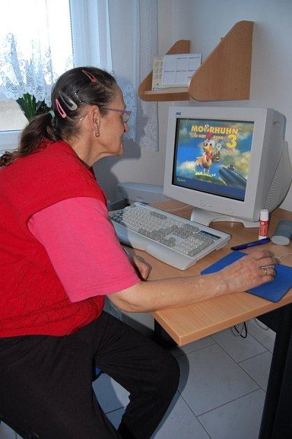 Senioři se učí pracovat na počítači.