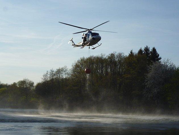 Ve svahu naproti železniční zastávce Chlum hořel les. Hasiči povolali vrtulník s bambi vakem.