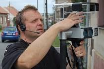 Vrchní strážník novostrašecké městské policie Martin Novák seřizuje radar před akcí.