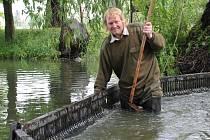 Miroslav Jelínek čistí výpusť u Velkého rybníka v Jesenici