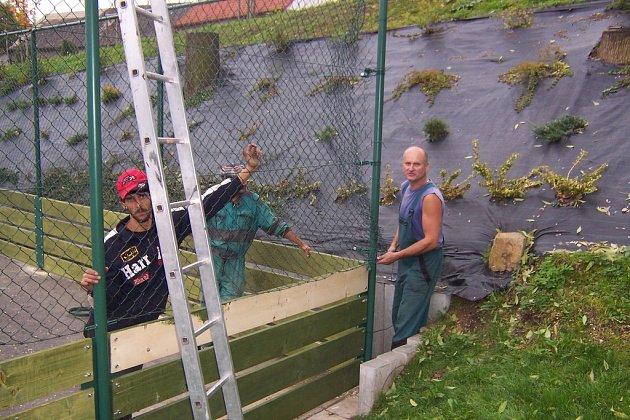 Dělníci dokončují oplocení hřiště.