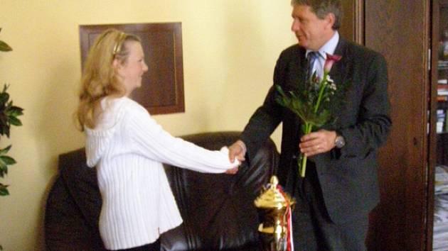 Starosta Zdeněk Nejdl předává Olivii květinu a gratuluje k úspěchu.