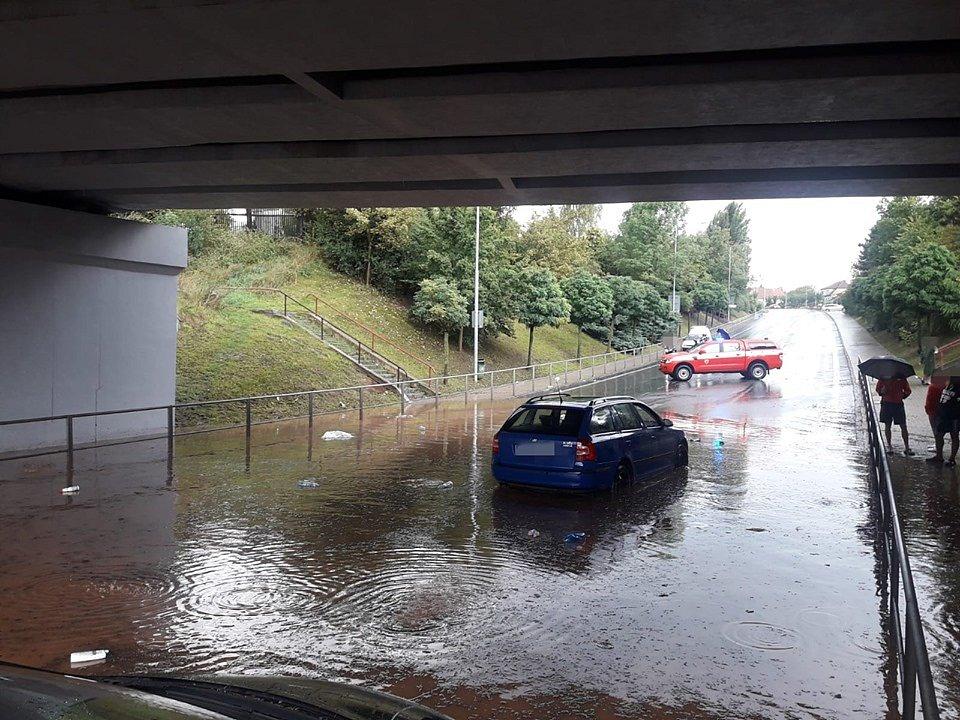 Silnici pod viaduktem zatopila voda a uvízla v ní vozidla.