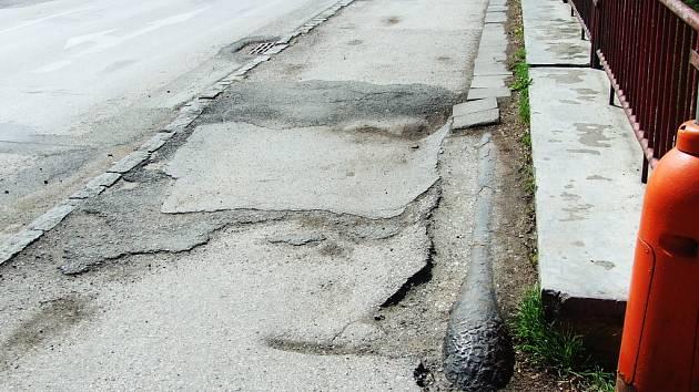 Propadlý chodník na mostu v Nádražní ulici.