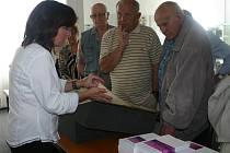 Renata Mayerová ředitelka rakovnického archivu ukazuje archiválie návštěvníkům