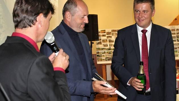 Ministr zahraničí Tomáš Petříček (vpravo) pokřtil knihu k 700. narozeninám Rakové. Asistoval mu senátor Pavel Karpíšek a zády je starosta obce František Bůcha.
