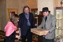 Návštěvnice výstavy přebírá od Jaroslava Páchy (vpravo), hlavního iniciátora expozice, karton templářských vín. V ruce už drží poukaz k pobytu v zámeckém hotelu pro dva.