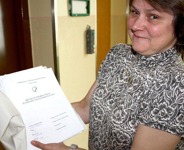 Marie Šamanová právě odnáší dokončené závěrečné písemné práce ze základů společenských věd.