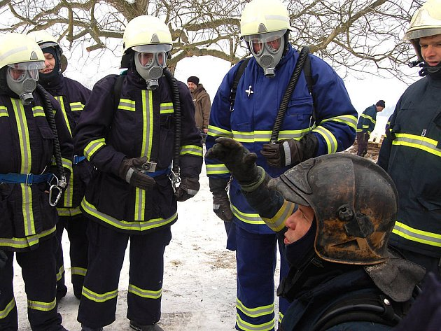 Velitel čtyřdenního cvičení v Přívěticích Jan Hora (v pokleku) nejprve vždy poučil zasahující kolegy. Dobrovolníci i profesionálové pak vnikli do zakouřené roubenky, kde podle námětu došlo k výbuchu par ethanolu a evakuovali postižené osoby.