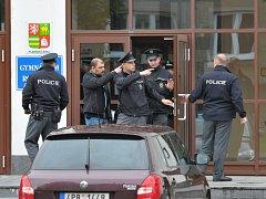 Policie opouští prohledanou budovu Gymnázia Rokycany a míří ke střední škole, která stojí jen pár desítek metrů vedle.