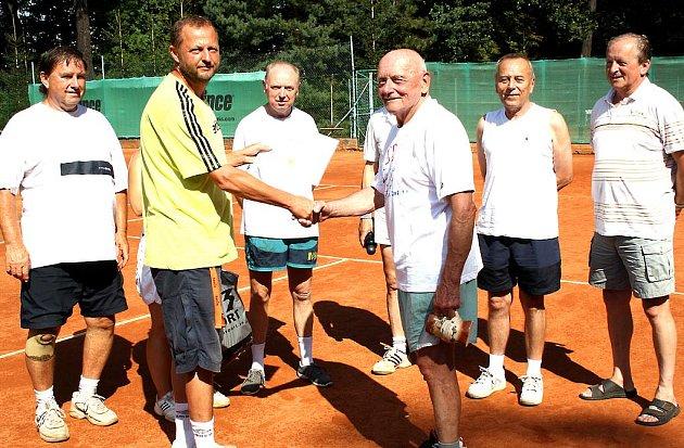 V rokycanských Alejích blahopřáli včera tenisté Jiřímu Vostrému (to je mladík v bílém tričku a se speciálním pohárem v ruce) k osmdesátým narozeninám. Vladimír Jedlička mu právě předává čestnou vstupenku do areálu, která bude platit do roku 2050.