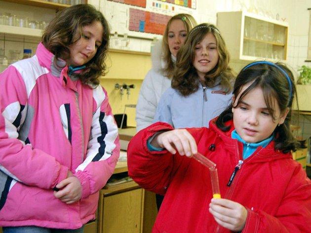 V gymnáziu otevřeli dveře v pátek i v sobotu. Míša Fenclová z Rokycan (vpravo v červeném) chodí sice teprve do třetí třídy, ale vyrazila na exkurzi se starší sestrou i rodiči. V chemické učebně si dokonce vyzkoušela pár pokusů.