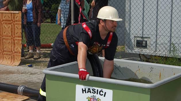 V NEVIDĚ se starali o sobotní dění dobrovolní hasiči. Ve sportovním areálu člen rakovského týmu ponořil hadici do kádě s vodou při požárním útoku.