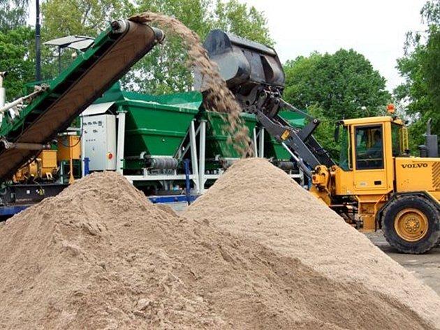 V rokycanských Husových sadech vrcholí rekonstrukce travnatého hřiště. Unikátní stroj se třemi násypkami  tu od včerejška chrlí přesně nastavenou směs ornice a písku jako podklad budoucí plochy.