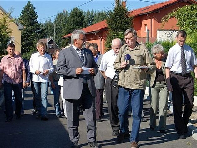 Starosta František Končel (v popředí) po úterním otevření nových asfaltových komunikací v Kařízku čelí tlaku spoluobčanů, kteří požadují opravu cest u jejich domů.