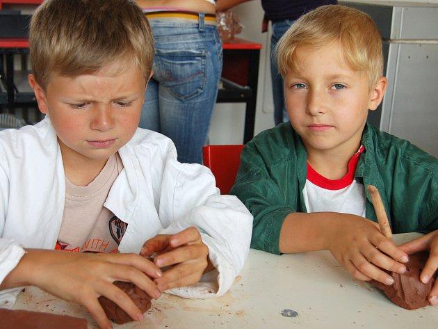 Výroba hrnce podle pravěkého vzoru byla jedním z témat příměstského tábora při DDm Rokycany. Hlínu si připravovali Lukáš Krš s Jardou Krýnerem(zleva).