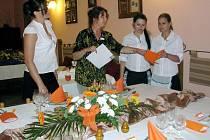 Číšníci ze Střední školy Jeřabinová před hosty ve Střelnici obstáli. Na snímku tabuli Veroniky Rottenbornové hodnotí Ivanka Vašáková a Dagmar Kfelířová (vlevo), přihlíží Jolana Veselá.