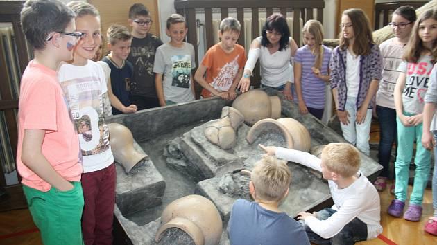 DO PRAVĚKU se vydali kluci a děvčata z devítiletky TGM v Rokycanech. Hlavní průvodkyní se jim stala Šárka Dvořáková. Na snímku čtvrťáky poučuje, jak se skladovalo obilí.