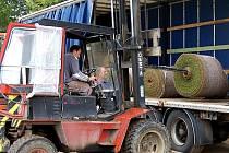 Pod dohledem Dalibora Šmída vykládá dělník pomocí vysokozdvižného vozíku  kamion s  travnatými pásy, dovezenými z Německa.  Ty  budou tvořit povrch nově zrekonstruovaného příkosického fotbalového hřiště.