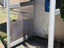 Rozbité sklo telefonní budky proti poště.