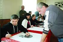 Při plískovské prakiádě se starosta obce Radek Škrdlandt (sedící) ujal rozhodcovské role a stejně tak i Dita Ševčíková (vedle). Sčítání nastřílených bodů přihlíží Karel Berka z Březové.