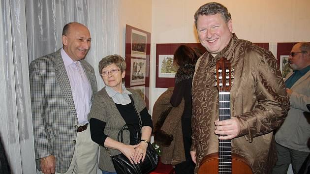 Vernisáž výstavy děl Jiřího Wintera Neprakty hrou na kytaru zpříjemnil Jan Irving (vpravo). Na snímku je s ním i Jaroslav Kopecký, znalec umělcova díla, a jeho manželka.