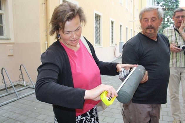Hana Hrachová (archivářka) po otevření makovice věže měřila uvnitř nalezené pouzdro s dokumenty.