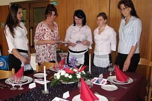 Aranžování slavnostních tabulí se v rámci praktické části závěrečných zkoušek ujaly číšnice Žaneta Ladičová (zleva), Tereza Senčáková, jejíž výkon právě hodnotí učitelka Iva Vašáková, a třetí zkoušenou byla Tereza Kdolská. Přihlíží Dagmar Kfelířová.