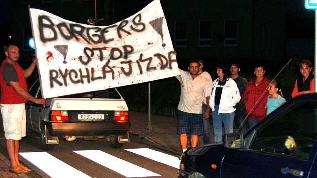 Zaměstnance Borgersu, mířící ve čtvrtek večer auty do práce,  vítal transparent.  Skupina místních se je snažila přimět ke zpomalení. Ve středu stál střet s autem jednu z nich i to nejcennější –  život. Na snímku je část demonstrujících.