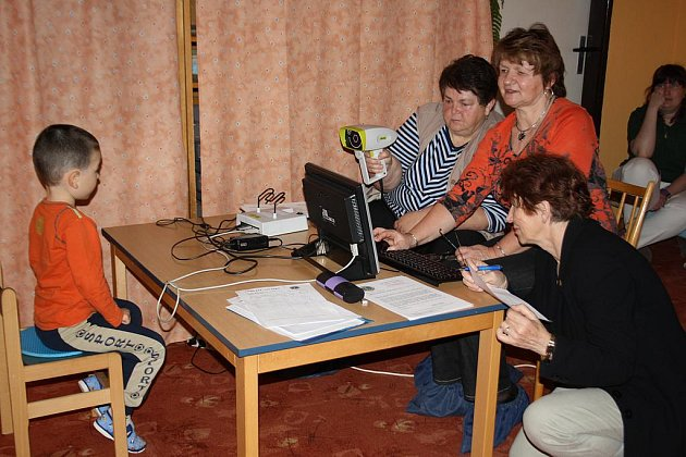 Screeningový binokulární autorefraktometr drží Blanka Rozumová, na monitoru sleduje  výsledky  Jitka Judlová.