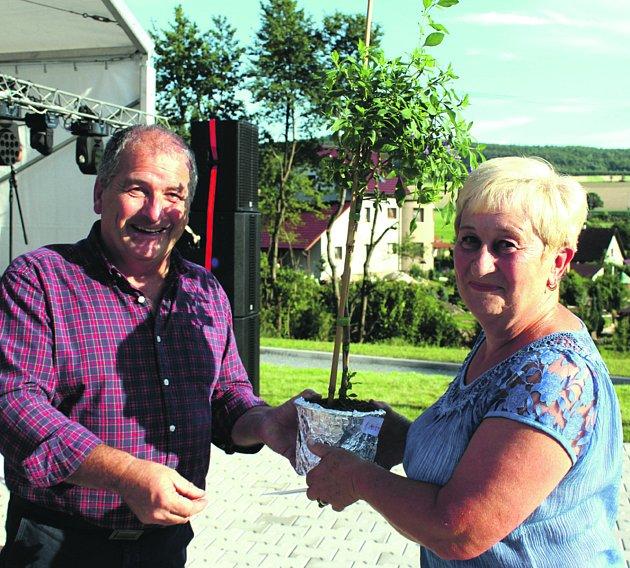 Markovi zvítězili v klabavské soutěži o nejhezčí rozkvetlou předzahrádku. Na snímku zástupkyně rodiny přebírá odměnu od sponzora soutěže pana Gustava.