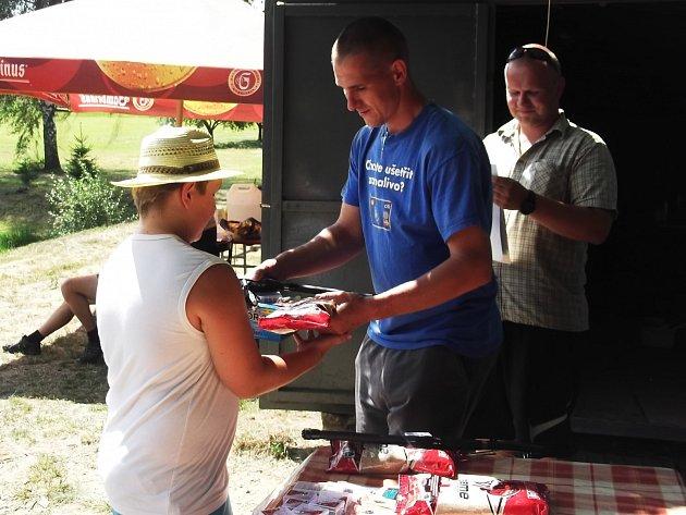 PETR OSVALD z Příkosic (vlevo) ovládl v sobotu dětské rybářské závody. Bral prvenství nejen za nejvíce úlovků, ale také za největšího kapra. Cenu v podobě prutu a krmení mu předává Jakub Heindl (uprostřed). Za ním vše kontroluje Martin Šefl.