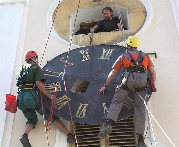 Před opravou. Hodiny na rokycanské radnici projdou v příštích několika měsících rekonstrukcí. Před tím je však museli včera z věže sundat horolezci Pavel Fromel a Robert Huňáček.