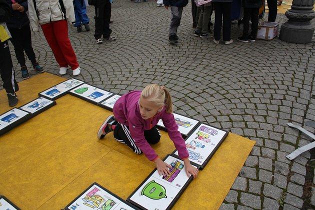 ANDREA MAŠÍČKOVÁ ze ZŠ Čechova v pátek dopoledne skládala obří domino na rokycanském náměstí.