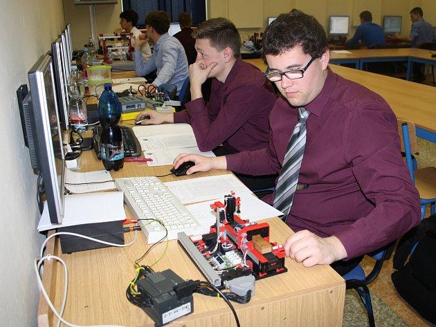 Na pořadu byla v úterý praktická maturita a studenti měli pomocí navrženého programu modely rozhýbat. V popředí snímku zápolí Martin Vyleta s kódovací linkou a Pavel Jedoun (vedle) si vylosoval programování pračky.