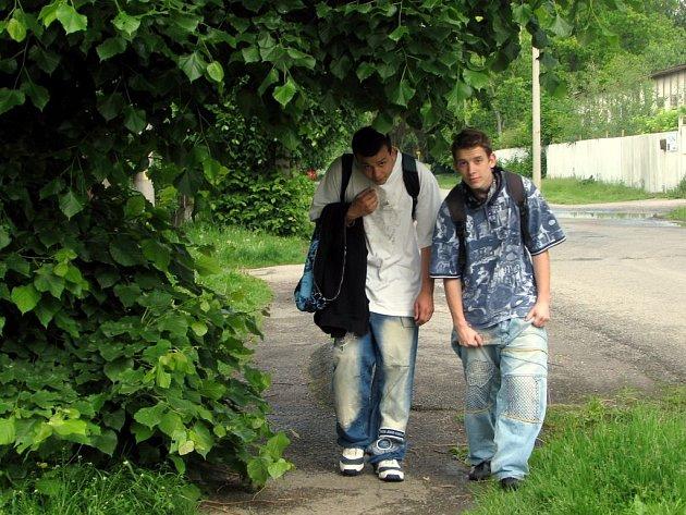 Nízko visící větve stromů v rokycanské Litohlavské ulici znepříjemňují lidem chůzi po chodníku. Skrčit se museli také Tomáš Cudrák a Václav Hrachovec (na snímku) a byli rádi, že neprší a voda jim  neteče za krk.