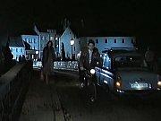 Kamenný most ve filmu večer. Učitelka kráčí ze školy domů.